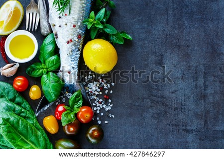 Close up of fish dishes cooking background with space for text. Fresh fish with various ingredients on dark vintage board, preparation. Flat lay. Healthy food or diet nutrition concept. - stock photo