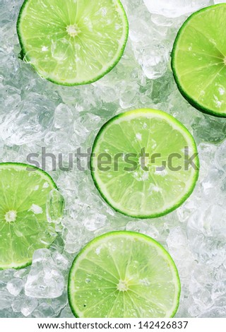 Close-up of five fresh slices of green limes over crushed ice cubes - stock photo