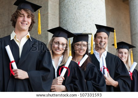 Close-up of five graduates students posing in front of the university - stock photo