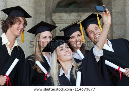 Close-up of five graduates taking a picture of themselves in front of the university - stock photo