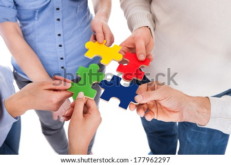 Close-up Of Five People Hand Holding Colorful Puzzle Over White Background - stock photo