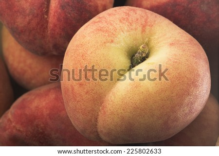 Close Up of flat peach on top of pile. - stock photo