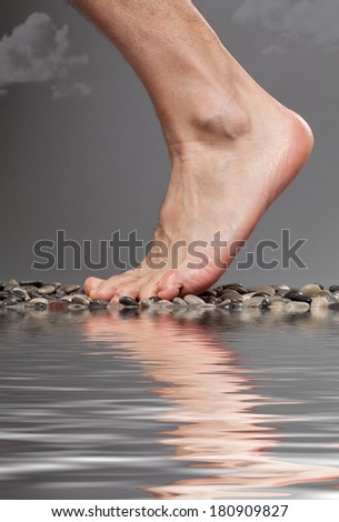 Close up of foot by the water on a stormy day - stock photo