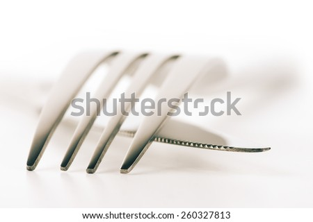 Close-up of fork and knife on white background. Soft focus, shallow DOF. Toned image. - stock photo