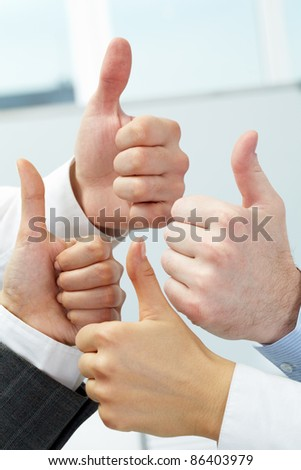 Close-up of four hands showing big thumbs - stock photo