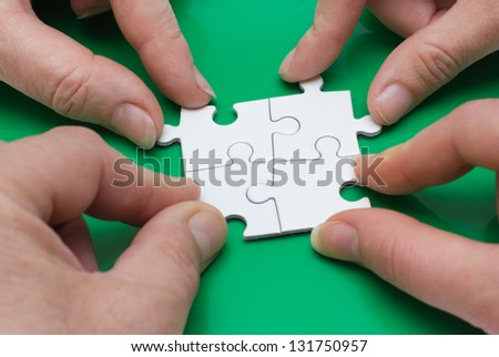 Close up of four people' hands with puzzle - stock photo