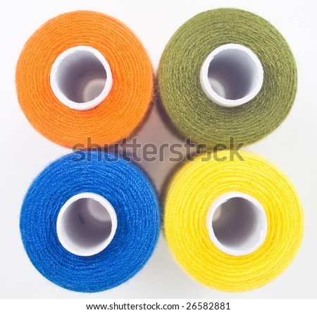 close up of four sewing spools - stock photo