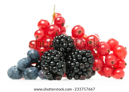 Close-up of fresh and nutritious berries as blueberries, blackberries and redcurrants, natural source of Vitamin C and antioxidants, on white - stock photo