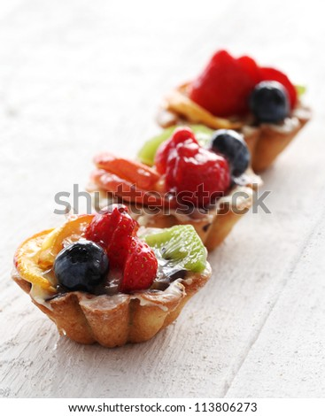Close up of fresh and tasty cakes with fruits and berries - stock photo