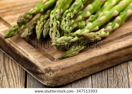 Close up of fresh asparagus on wooden server board. Selective focus on tips of asparagus.  - stock photo