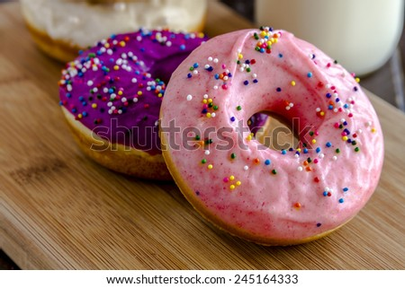 Close up of fresh baked vanilla bean donuts with colorful icing sitting on wooden cutting board with glass of milk - stock photo