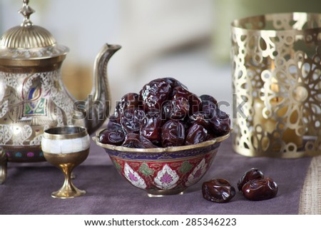 Close-up of fresh dates in ornamental bowl with kettle and cup on a tablecloth - stock photo