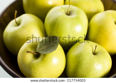 Close up of fresh green golden delicious apples in brown basket, view from top. - stock photo