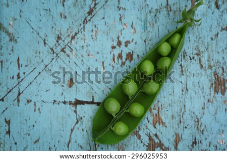 Close-up of fresh green pea on blue wooden background - stock photo