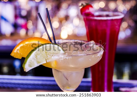 Close up of fresh lime margarita with ice cubes in margarita glass sitting on bar top garnished with orange and lime wedges and strawberry vodka drink in background - stock photo