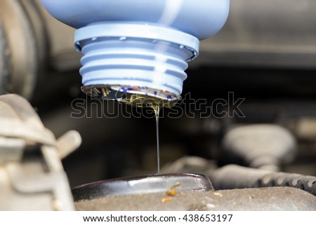 Close up of fresh oil being poured into a car dirty and dusty motor - stock photo