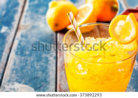 Close Up of Fresh Orange Frozen Granita Slush Drink Garnished with Orange Wedge and Served in Glass with Striped Straw on Weathered Blue Wooden Picnic Table with Oranges in Background - Copy Space - stock photo