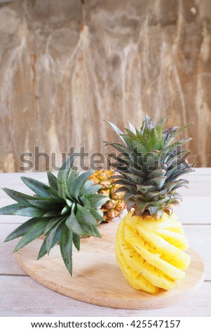 Close up of fresh pineapple with cover and fresh peeled off pineapple on wooden background - stock photo