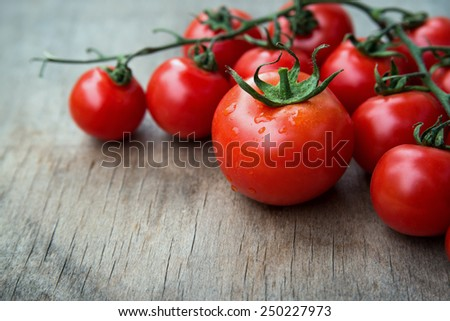 close up of fresh red delicious tomatoes  on an  old wooden tabletop background with place for text - stock photo