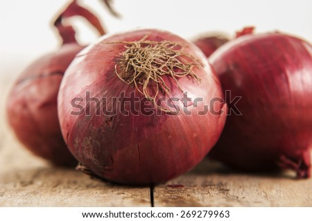 Close-up of fresh red onions on a wooden background - stock photo