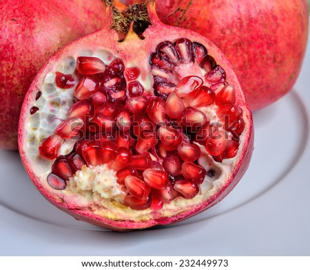 Close up of fresh ripe juicy pomegranate fruit on the white plate isolated on white background, selective focus.  - stock photo