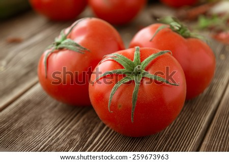 Close-up of fresh, ripe tomatoes on wood background - stock photo