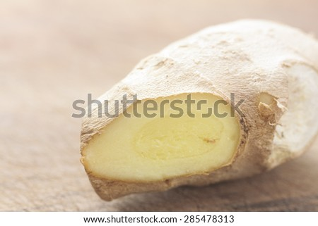 Close-up of fresh root ginger on a wooden surface - stock photo