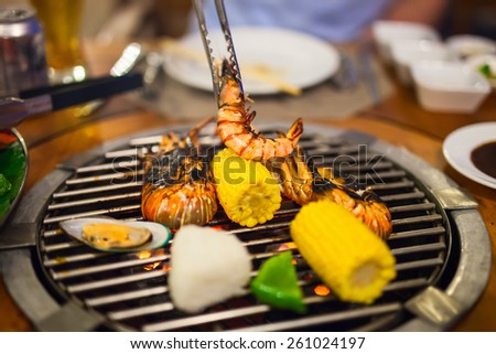 Close up of fresh seafood and vegetable preparing on grill - stock photo
