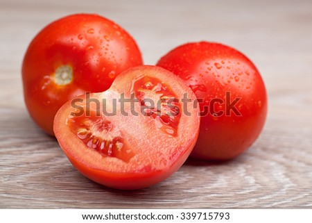 Close up of fresh tomatoes in drops of water on a wooden board - stock photo