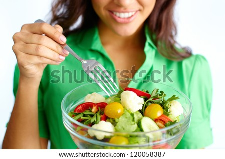 Close-up of fresh vegetable salad being eaten by female - stock photo