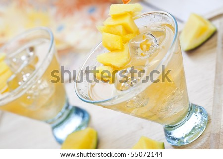 Close up of freshly made mango cocktail with small pieces of fruit - stock photo