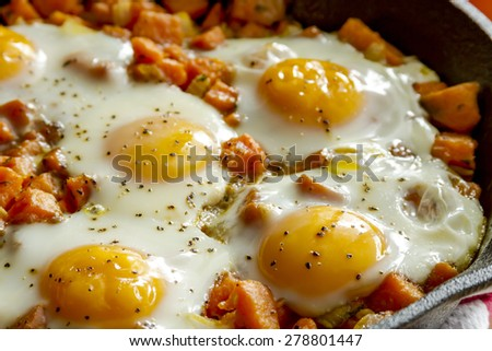 Close up of fried eggs and sweet potato has in cast iron skillet - stock photo