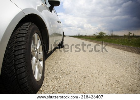 Close-up of front wheel of the car on narrow road in countryside with clouds in background - stock photo