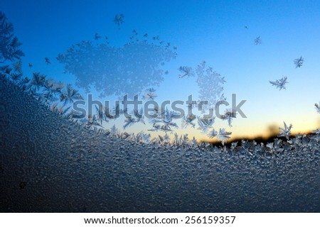 close-up of frost on the glass against the blue sky  - stock photo