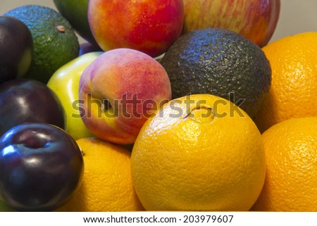 Close up of fruit, plum, avocado, peach, nectarine, apple, and oranges - stock photo