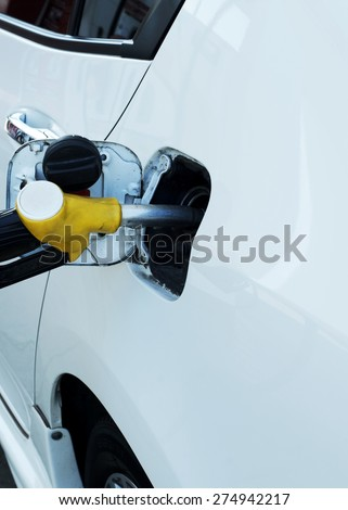 Close up of Fuel nozzle into fuel tank for car refueling - stock photo