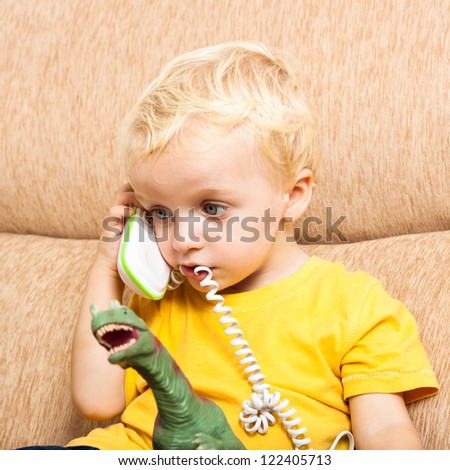 Close up of funny cute child boy playing with phone. - stock photo