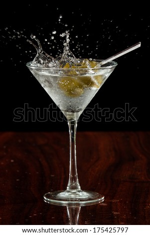 close up of  garlic stuffed martini olives splashing into a cocktail over a dark background - stock photo