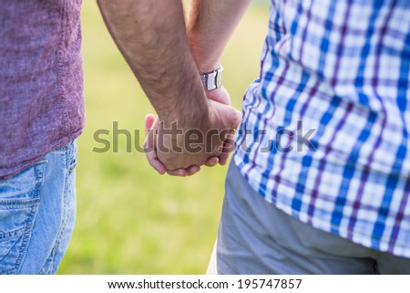 Close up of Gay couple holding hands outdoor - stock photo