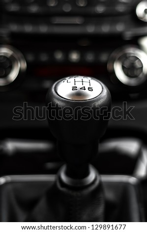 close-up of gearstick inside a car against cockpit and dash - stock photo