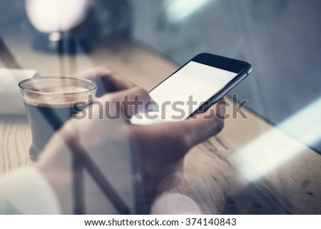 Close up of generic design smart phone holding in female hands for texting message. Cup coffee on the table - stock photo