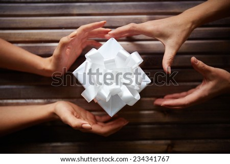 Close-up of gift box among two pairs of hands - stock photo