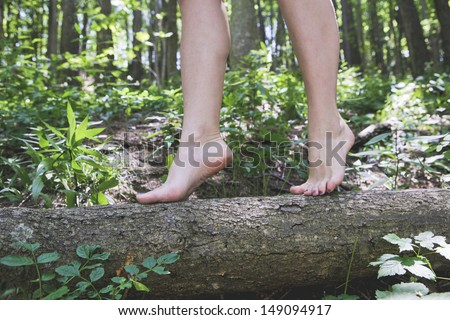 Close up of girl bare feet walking on a tree trunk - stock photo