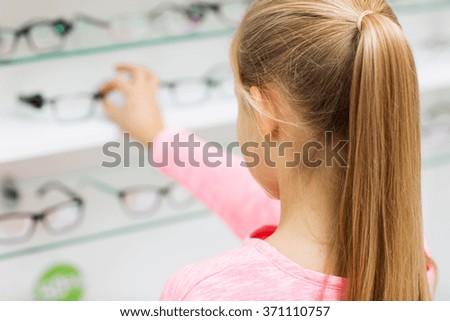 close up of girl choosing glasses at optics store - stock photo