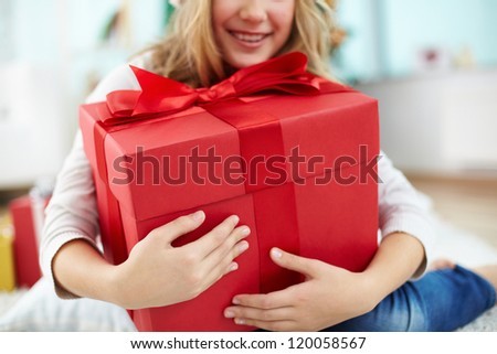 Close-up of girl holding big red giftbox - stock photo