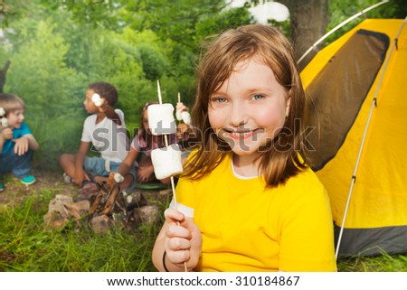 Close-up of girl holding stick with marshmallows - stock photo