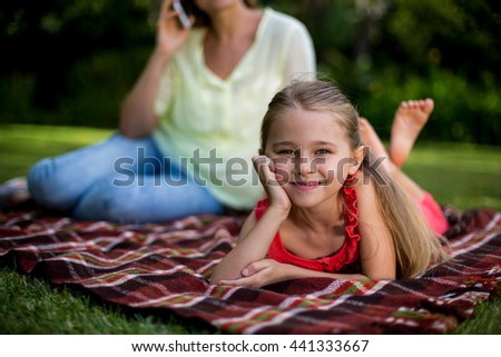 Close-up of girl lying on blanket while mother sitting in background - stock photo