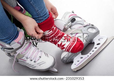 Close-up of girl preparing for ice skating - stock photo