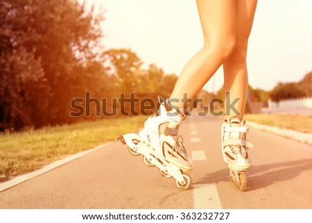 Close up of girl rollerblading in park on sunny day, strong colorful tonal photo filter correction.  - stock photo
