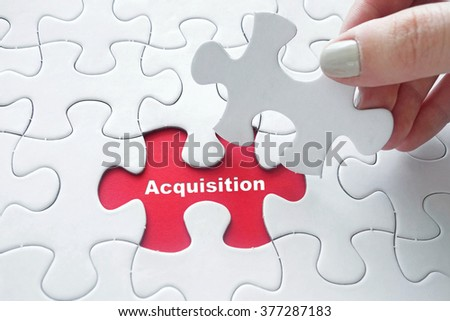 Close up of girl's hand placing the last jigsaw puzzle piece with word Acquisition - stock photo
